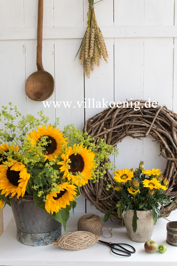 Herbstblumen mit Weidenkranz vor einer Holzwand dekoriert