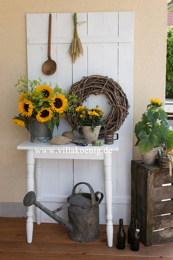 Herbstliche Dekoration mit Sonnenblumen und Mittagsgold vor Holzwand
